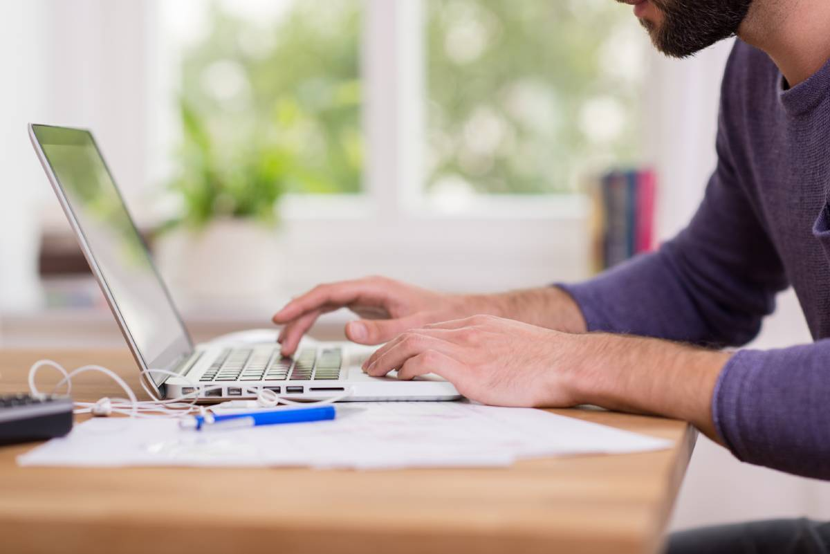 A man working from home at his table while using a laptop