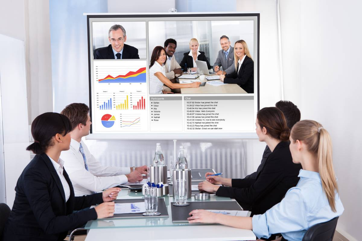 Four business people collaborating with coworkers via video conference