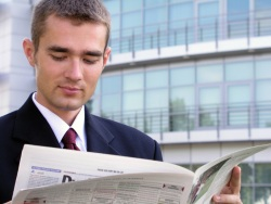 Businessman reading newspaper in front of an office building